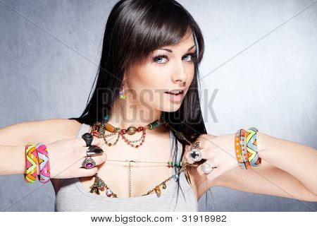 cute  girl with lot of necklaces, bracelets and rings studio shot
