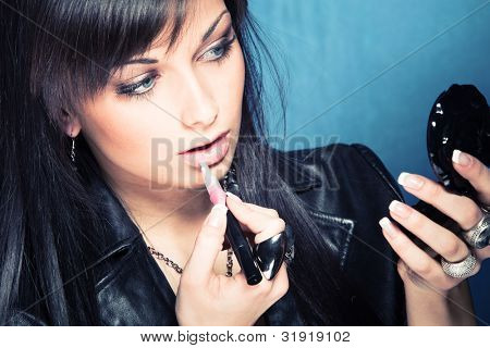 young woman apply lipgloss studio shot