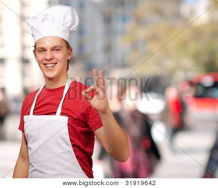 portrait of young cook man doing success symbol at crowded street
