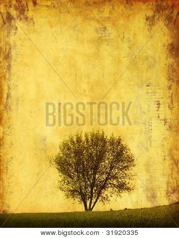 Grunge image of a tree on a hill.