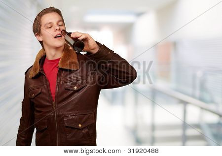 portrait of young man drinking beer at entrance of modern building