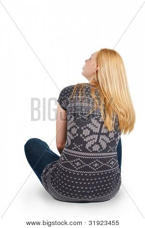 Back view of beautiful young woman sitting on the floor and looks into the distance. Blonde girl relaxes. Rear view people. Isolated over white background.