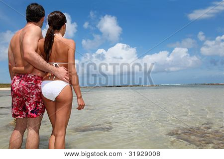 Couple in swimsuit standing by a lagoon