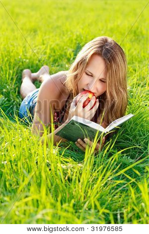 Happy Woman Reading Book With Apple In Hand