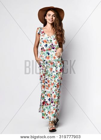 poster of Luxurious Young Slim Girl With Long Hair In A Long Dress With A Floral Print And A Straw Hat. Gettin