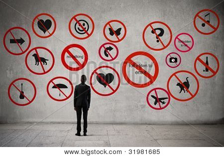 Young businessman standing in front of many prohibitions