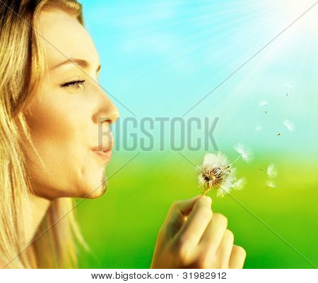 Happy beautiful woman blowing dandelion over blur background, having fun and playing outdoor, teen girl enjoying nature, summer vacation and holidays, young pretty female holding flower, wish concept