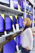 stock photo of televisor  - Blonde girl wearing scarf looks at plasma TVs in supermarket - JPG