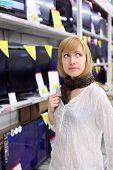 picture of televisor  - Blonde girl wearing scarf thinks about buying TV in supermarket - JPG