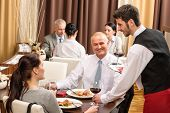 Young waiter serve wine to business people at professional restaurant