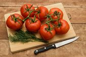 Tomatoes Lie On A Cutting Board. Nearby Lies A Green Dill. The Board Lies On A Natural Wooden Backgr poster