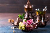 Traditional Turkish Sweets With Tea Mint In A Traditional Glass On A Concrete Background poster