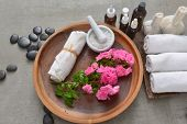 Branch pink rose ,rolled towel ,herbal ball,salt in bowl in wooden bowl with black stones , oil bott poster