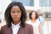 Serious Young African American Businesswoman. Portrait Of Confident Female Boss Standing With Collea poster