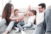 parents play with children sitting on the carpet in the living room poster