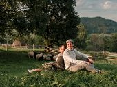 Young Wedding Romantic Couple Of Bride In White Dress And Bridegroom In Suit On Pasture Of Sheeps. W poster
