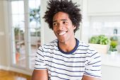 African American man wearing stripes t-shirt smiling looking side and staring away thinking. poster