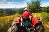 Man Driving Tractor In Agricultural Fields. Agricultural Worker Driving Tractor In Nature. Man Worki poster