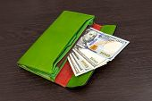 Big Green Wallet With Money On A Brown Background. The Wallet In Which The Dollars Lie. Concept Of S poster