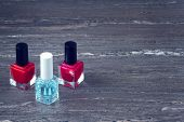 Close-up Image Of Two Red Nail Polish Bottles And One Colorless Nail Polish Bottle On Grey Wooden Ba poster