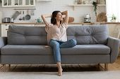 In Cozy Living Room Happy Woman Sitting On Couch Alone poster