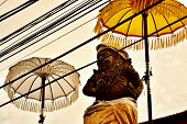 Praying Stone Statue Between Two Umbrellas On The Roof Of The Temple In Ubud. Bali, Indonesia. poster