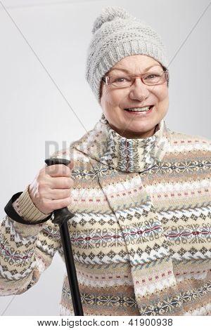 Glückliche alte Dame in Winterkleidung Wandern, Lächeln.