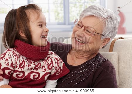 Grandmother and granddaughter laughing, looking at each other.