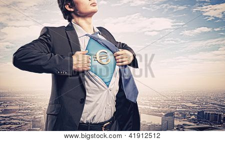 Image of young businessman in superhero suit with euro sign on chest