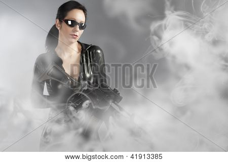 Sexy woman holding gun with helmet over smoke