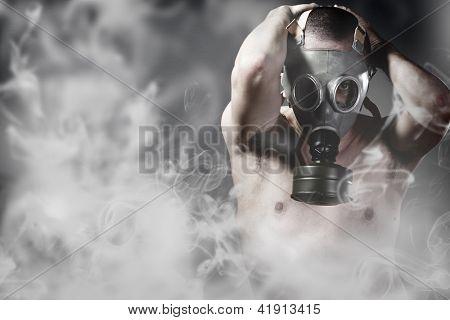 Porträt eines Mannes in einem verschmutzten Ambiente mit Gasmaske