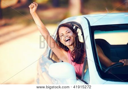 Happy woman waving from drivers seat in car while traveling
