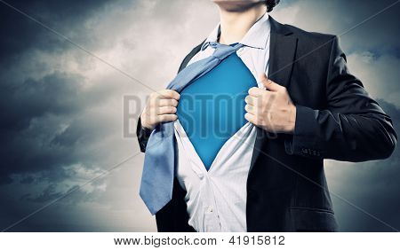 Image of young businessman showing superhero suit underneath his shirt