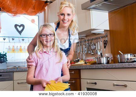 Mutter und Tochter kochen zusammen, sie machen Lasagne