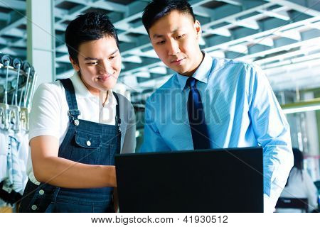 Chinese Worker or production manager and owner, ceo or controller, look on a laptop in a textile factory