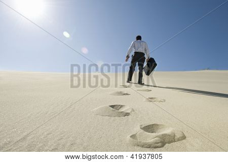 Low angle view of a businessman walking with briefcase in desert
