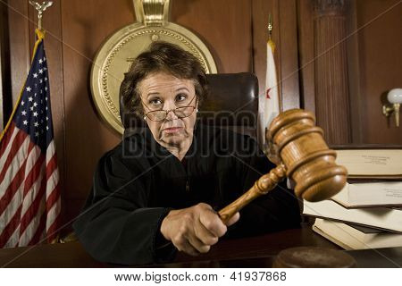 Senior Caucasian judge holding mallet in courtroom
