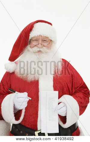 Portrait of a senior Santa Claus standing with paper and pen isolated over white background