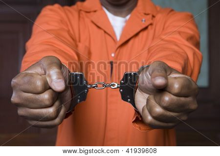 Midsection of prisoner's hands fettered with handcuffs