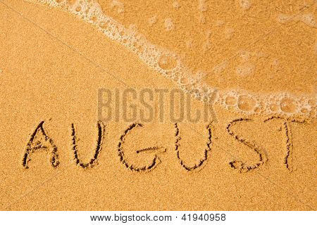 August - written in sand on beach texture - soft wave of the sea.