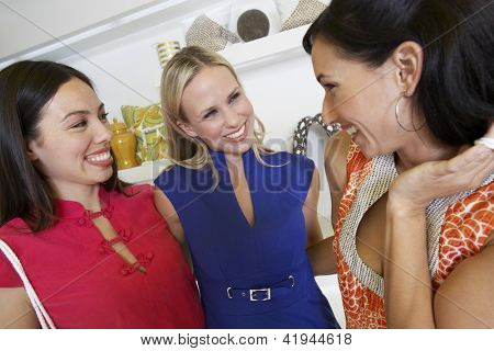 Portrait of female friends standing together in clothing store