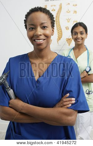 Happy female doctor holding otoscope with nurse in the background