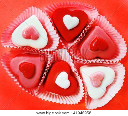 Heart shaped candies over red