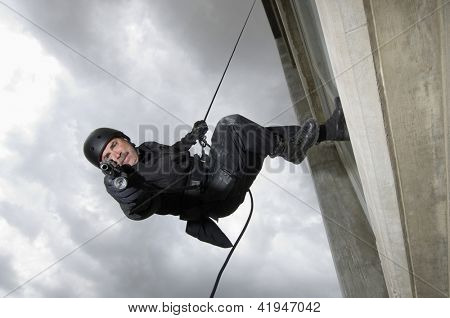 Portrait of commando aiming handgun while rappelling down the building