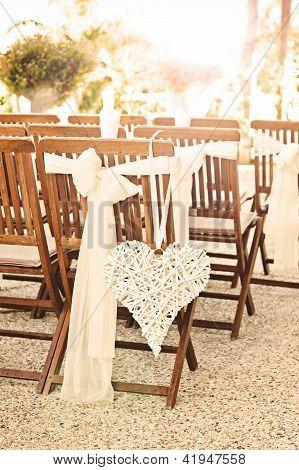 Um coração pende de uma cadeira em um casamento