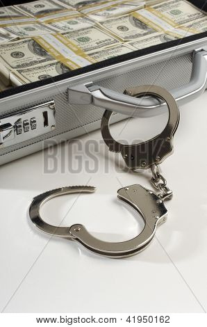 Suitcase full of dollars and handcuffs, studio shot