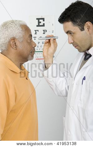 Male doctor testing patient's eye in clinic