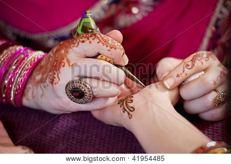 Artist Applying Henna to the Palm of a Woman's Hand