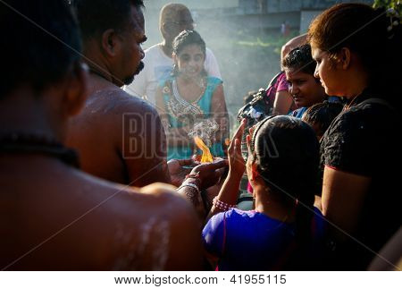 KUALA LUMPUR - JANUARY 27: A Hindu priest prays and blesses a family in preparation for their walk to the Batu Caves temple in Malaysia on January 27, 2013 during the Thaipusam festival.