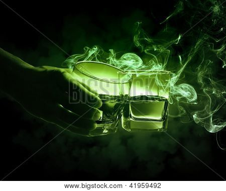 Hand holding one of two glasses of green absinth with fume going out